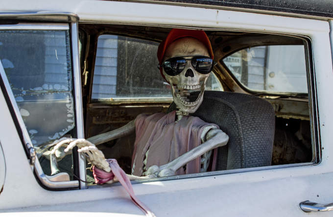 Skeleton looking at you inside an old car wearing a cap and sunglasses with its mouth open