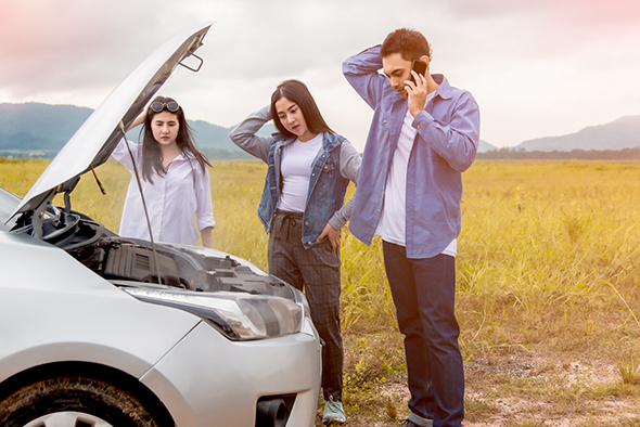 Two young women and a young man scratching their heads in front of a car with an open hood on the side of the road